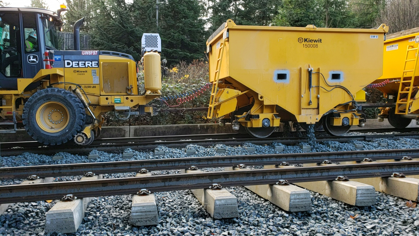Crews use a high-rail vehicle and ballast cars to 'flood' the rail with ballast.