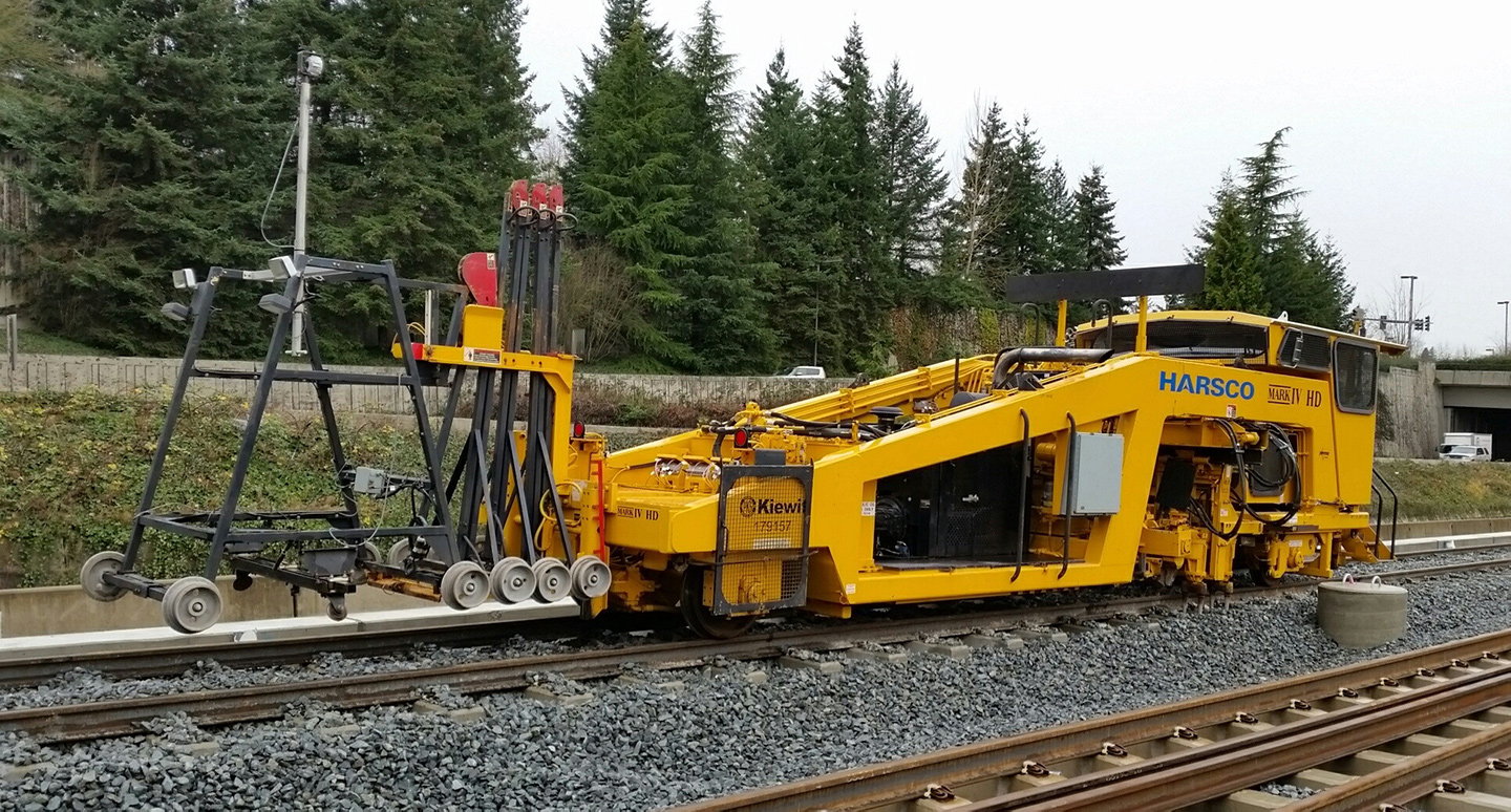 A machine called a 'tamper' uses lasers to measure the height of the rail lifts the concrete ties to the correct height.