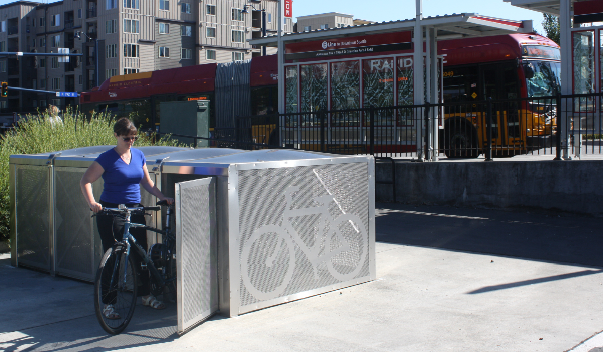 A bike rider loads his bike into an on-demand bike locker.