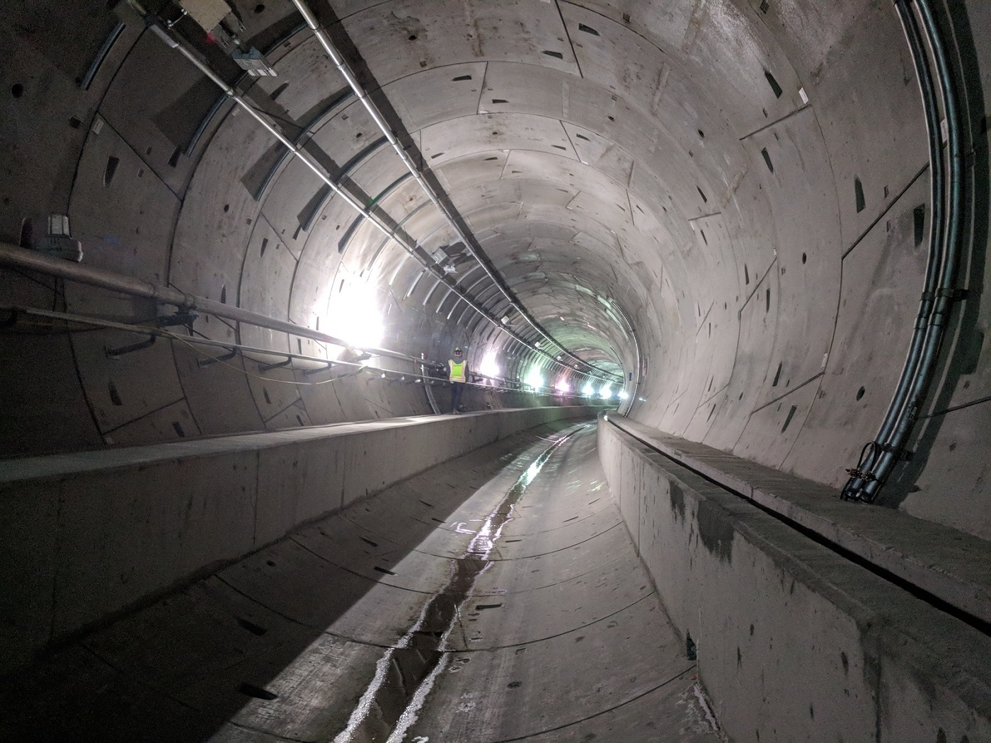 Worker walking in the empty Northgate tunnels prior to rail installation