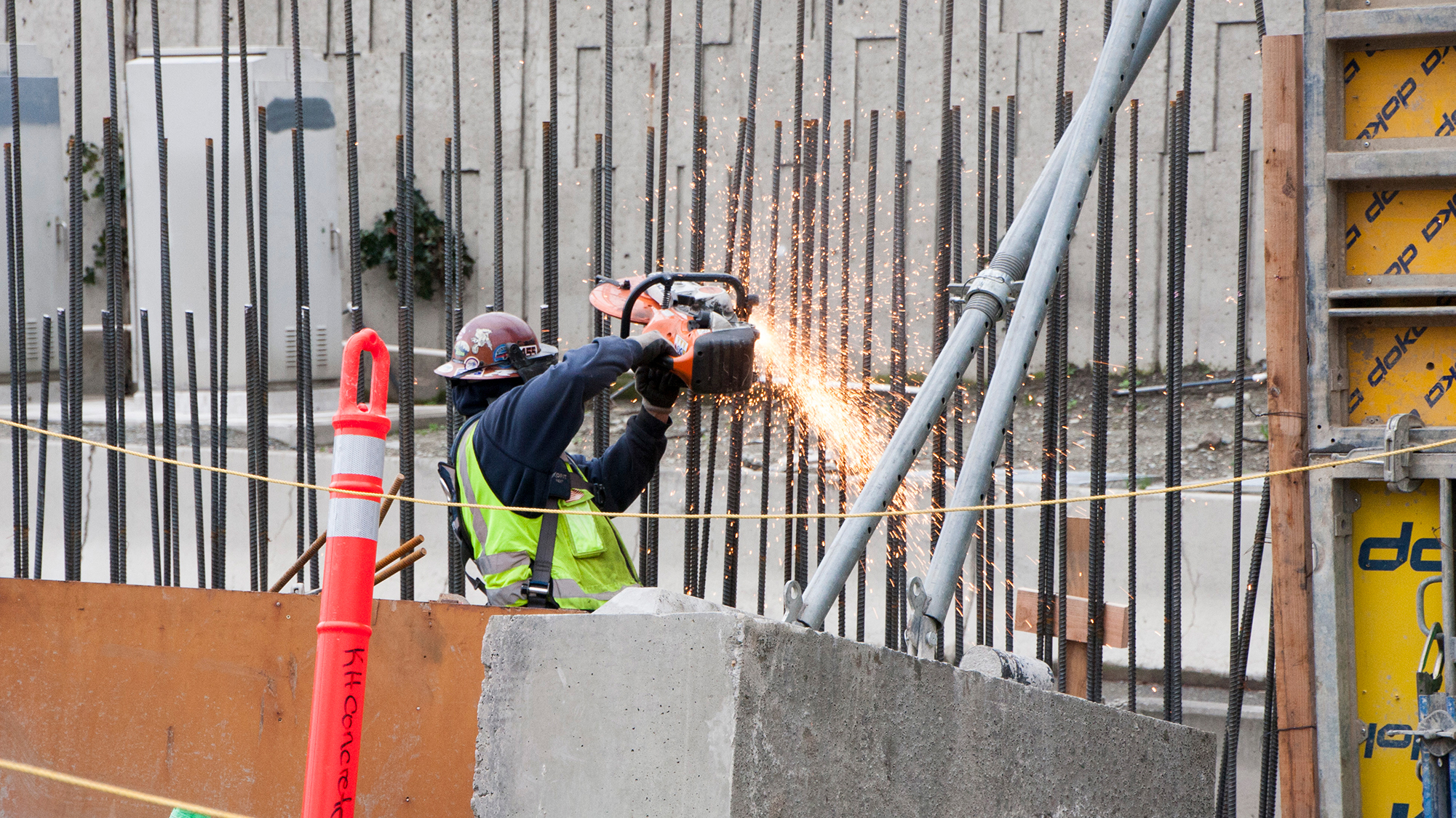 An iron worker cuts rebar for installation of the concrete sound wall at the Mercer Island station.