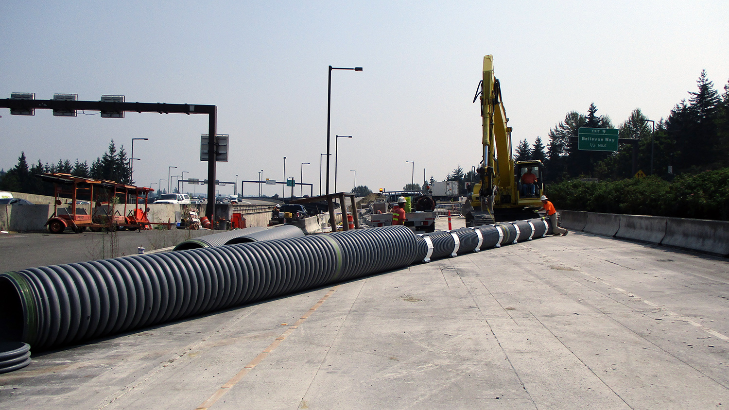 Crews install protective casing for utility lines near the future Mercer Island station.