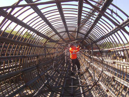 Worker ties rebar cage ahead of column work at Northgate Station site.