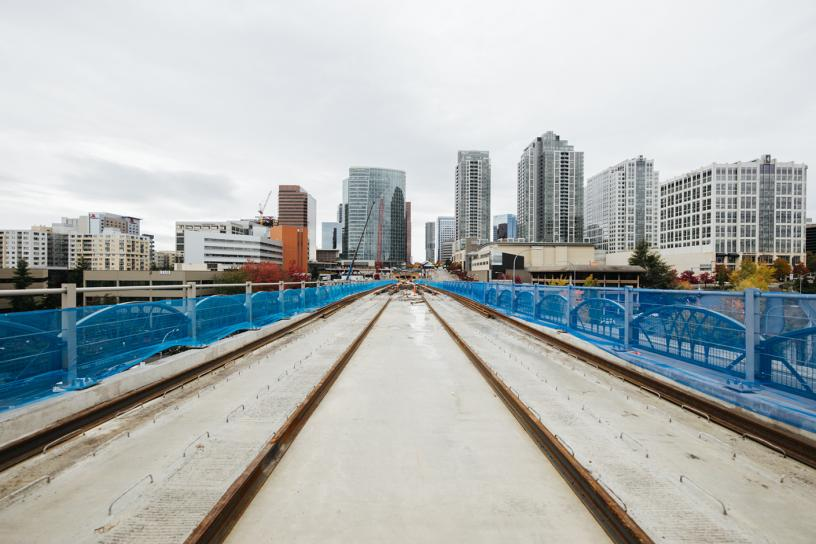 Link light rail tracks that are under construction; concrete, metal rails, construction equipment and fencing are visible. The tracks lead straight to downtown Bellevue will tall buildings visible in the background.