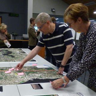 Community members look at maps and ask questions at an I-405 Bus Rapid Transit community meeting.