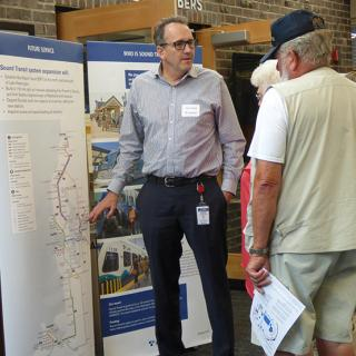 Community members discuss the I-405 BRT project with Sound Transit outreach staff.