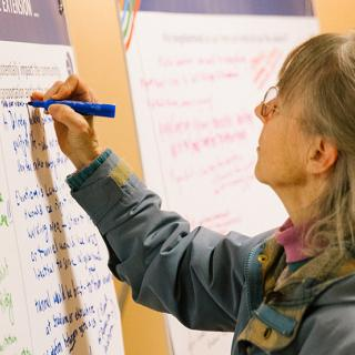 A community member makes notes on a project display for the West Seattle and Ballard Link Extension project.