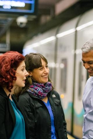 Riders chat at the Capitol Hill Station light rail station with Link train in the background.