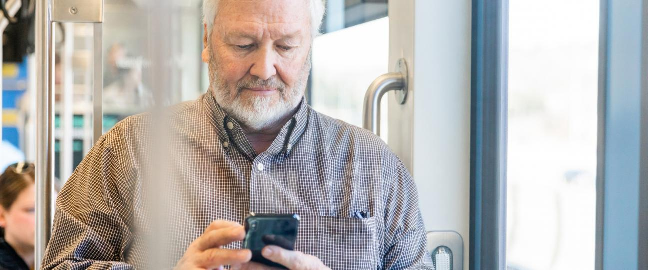 Link light rail rider uses his mobile device.