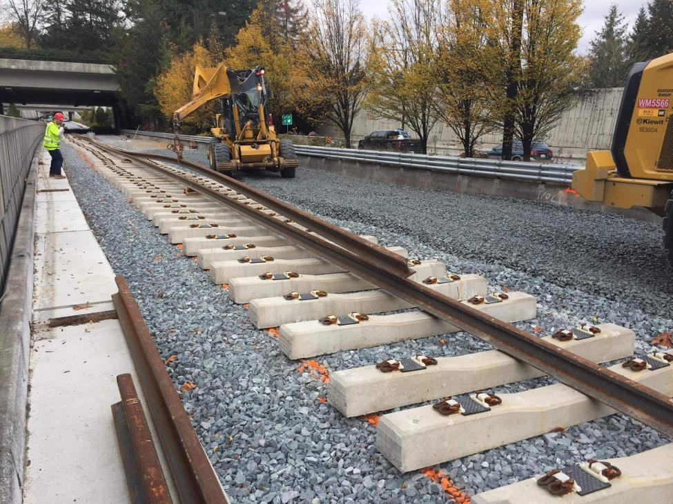 Workers installing rail on Mercer Island as part of the East Link light rail extension