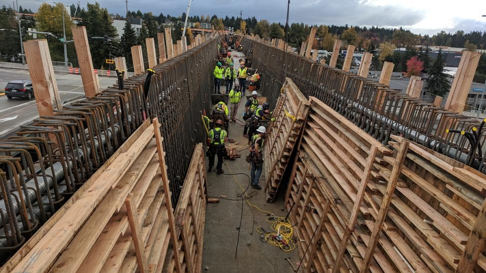 Crews busy inside the bridge over I-405 placing wood forms against the rebar cages waiting to be filled with concrete.