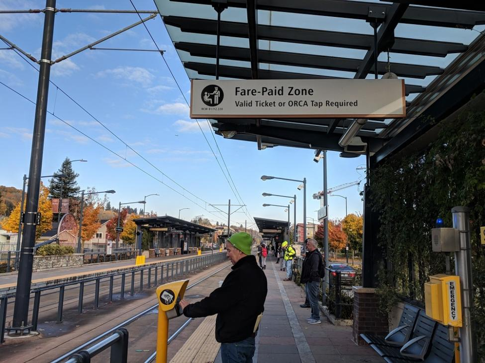 A rider taps his ORCA card at the reader at the Columbia City Link light rail platform