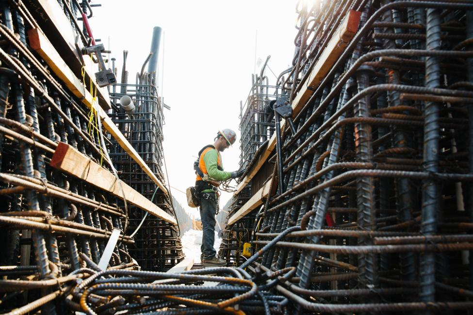 2018 in review: a worker wires rebar together for the new bridge over I-405.