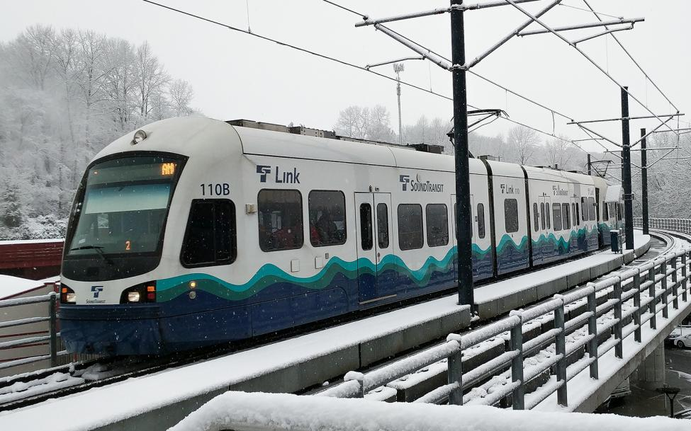 A link train approaching Mount Baker Station in the snow