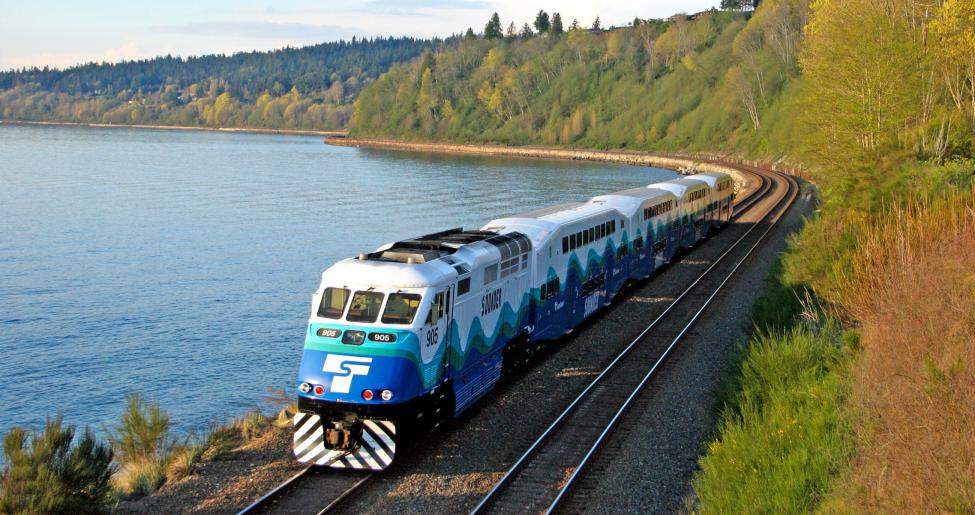Sounder Everett train moving on tracks surrounded by trees and a lake.