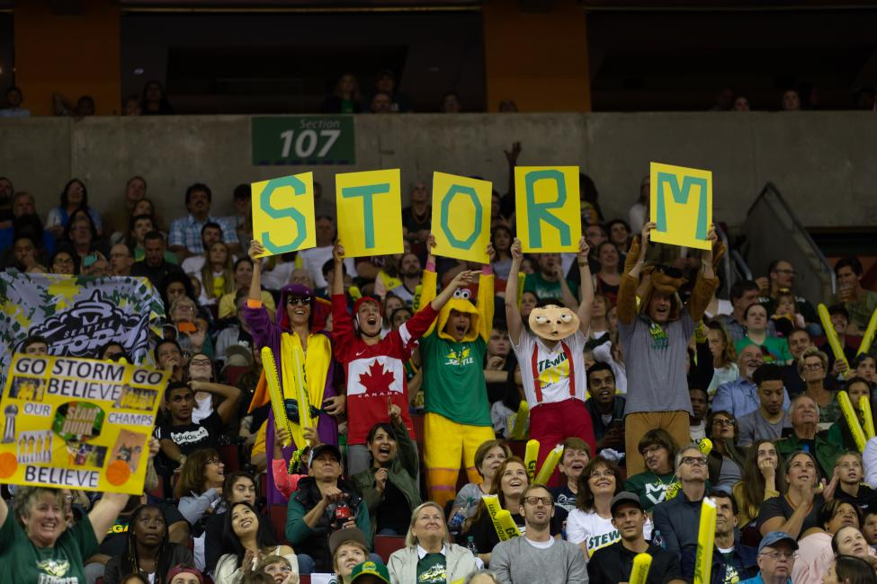 Image of fans holding up signs at a Seattle Storm game