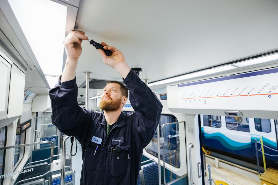 A maintenance crew member installs new LED lights on a Link light rail train