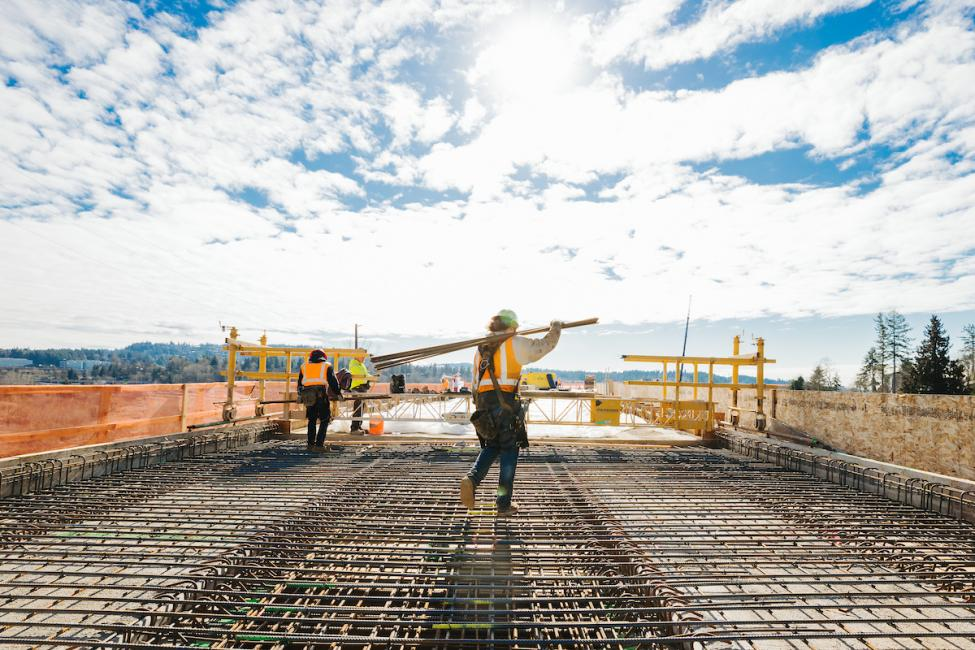 A construction worker carries lumber across the future platform at the future South Bellevue Station site.