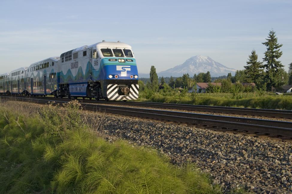 A Sounder train rolls through fields with Mt. Rainier in the background