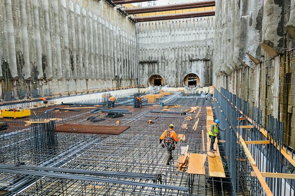 U District Station under construction in 2017 appears as a giant hole in the ground with a maze of steel bars across the bottom. It opens for service in 2021.