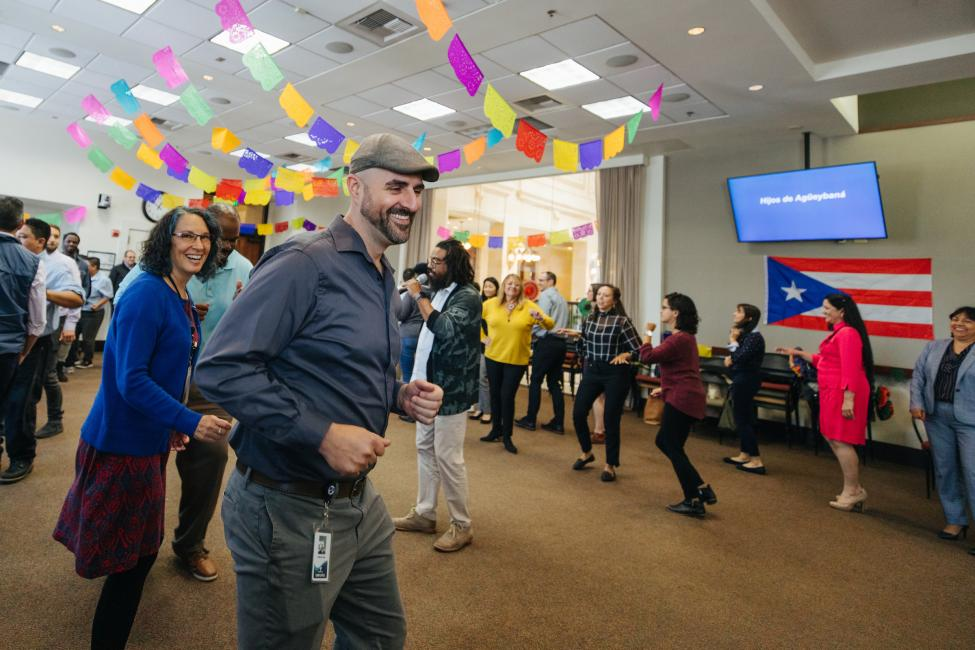 Sound Transit employees, including Jefferson Rose, dance at a Latinx Heritage Month kickoff celebration in a large room decorated with colored tissue paper banners and flowers.