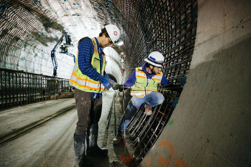 Two construction workers measure the wall of the tunnel under Downtown Bellevue.