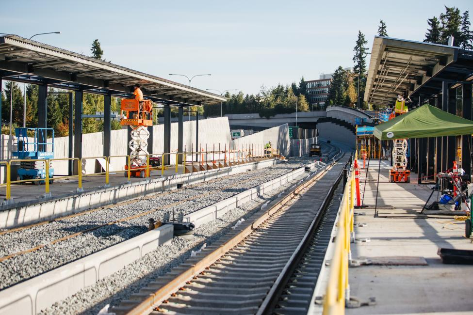 Workers can be seen in the background of this photo of Overlake Village Station, where rail and platforms are under construction.
