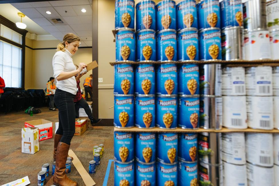 A woman, Ariel Taylor, helps build a structure out of canned food.