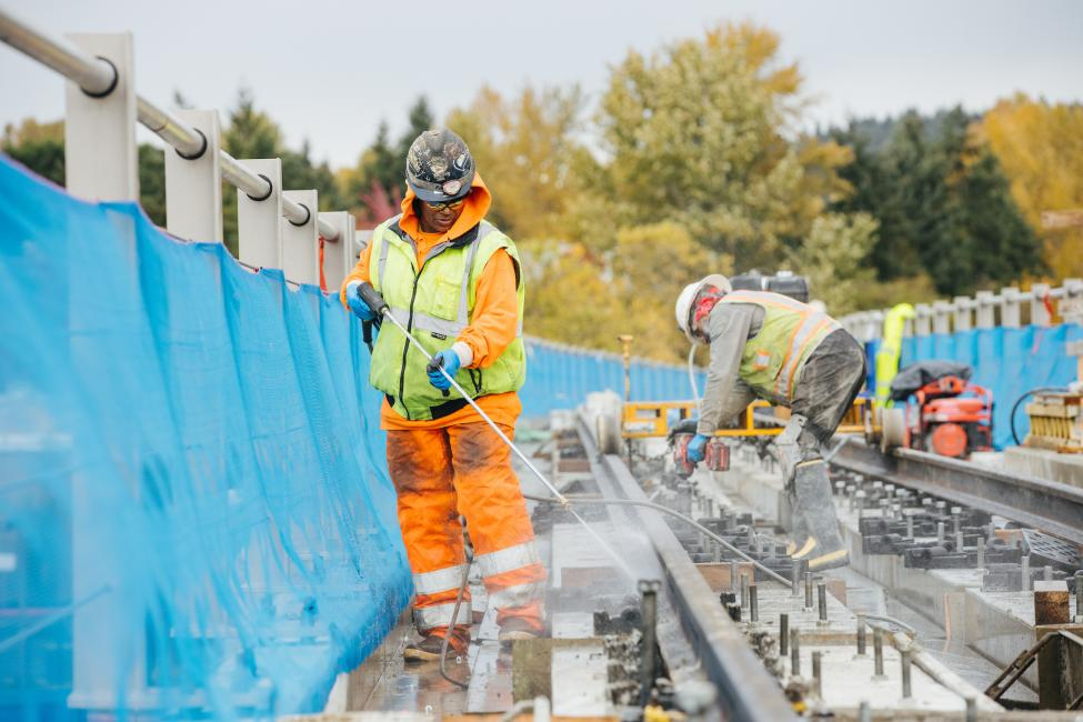 A construction worker sprays water at the rails being installed near Wilburton Station.