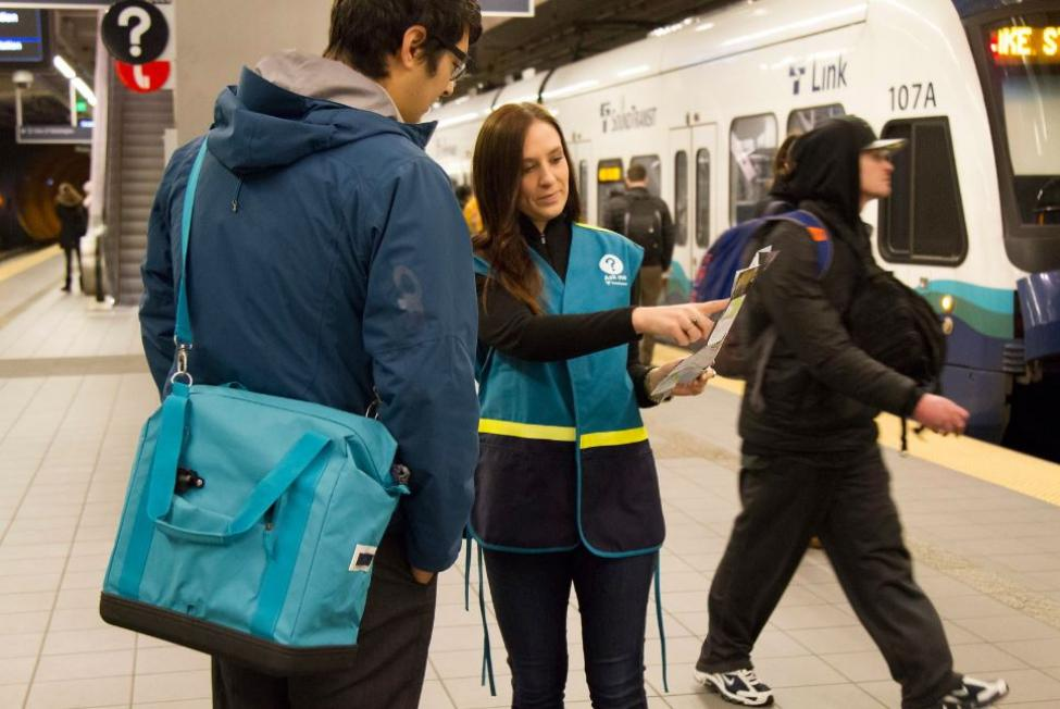 A Sound Transit employee in a blue vest directs a rider on how to use light rail.