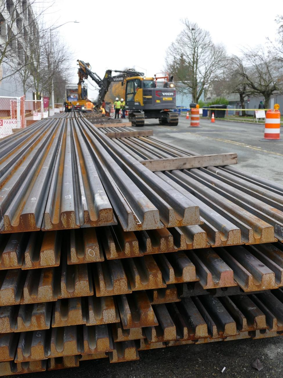 Stacks of rail are pictured, with construction equipment in the background.