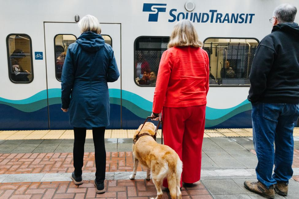 A woman with a cane and a woman with a seeing eye dog wait for the train.