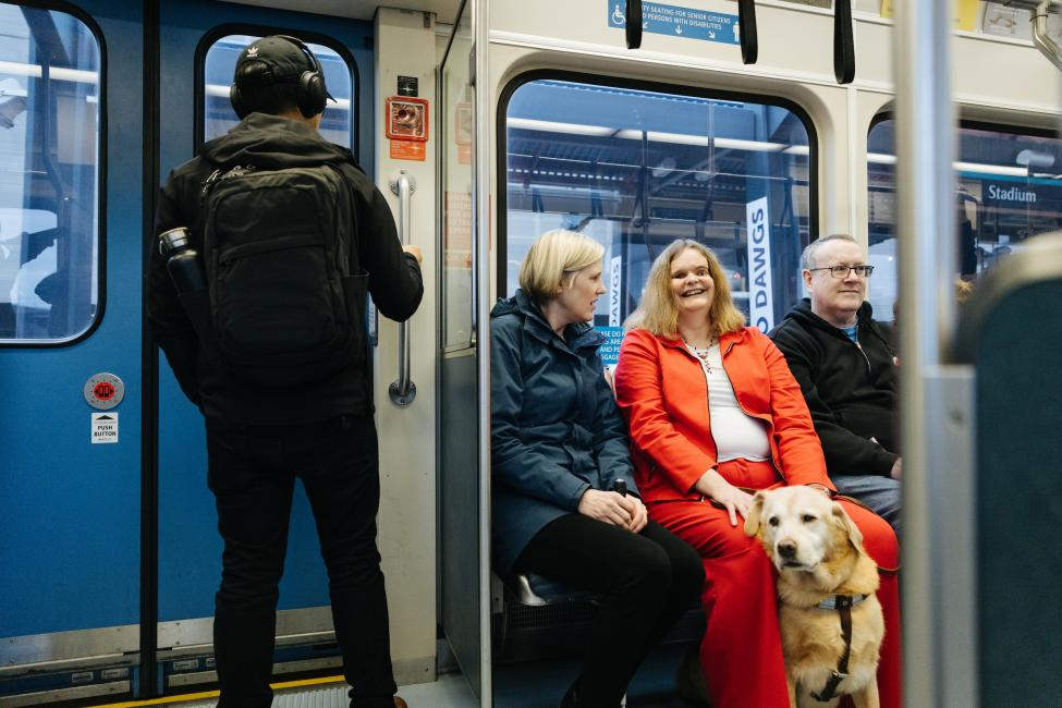 A woman with a seeing eye dog sits in the priority seating section of a Sound Transit light rail vehicle.