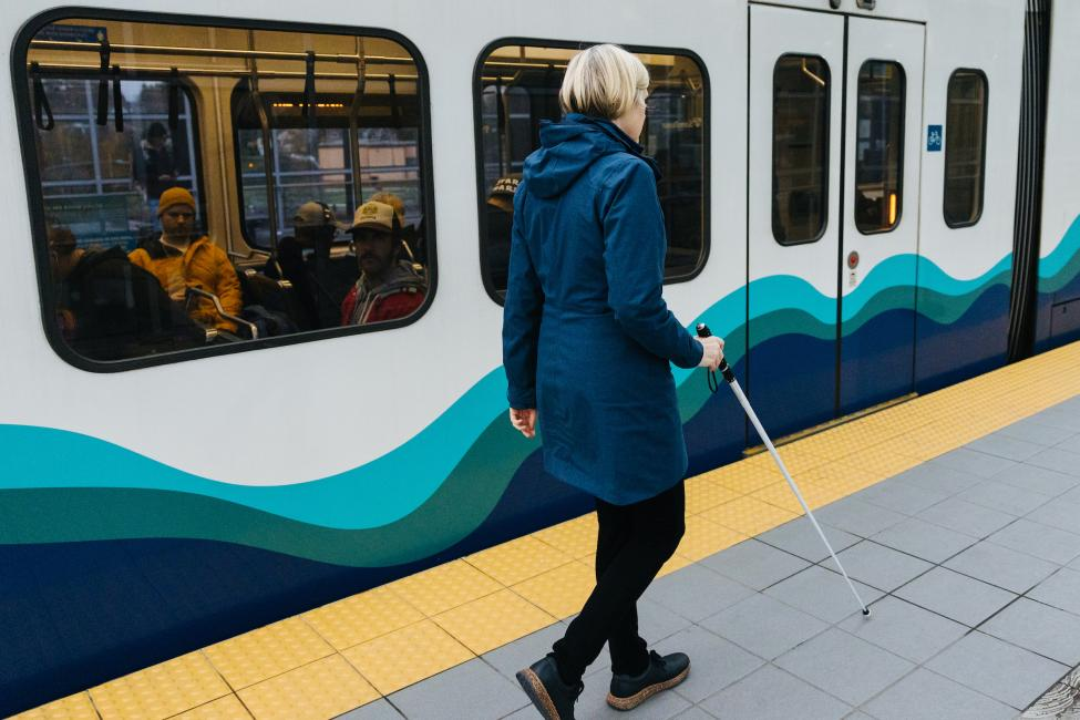 A blind woman uses a cane and tactile warning mat to navigate through a Link station.