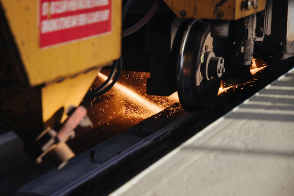Sparks fly as a rail profiling machine travels down the tracks during the rail grinding process.