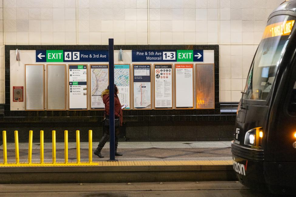 A rider walks past new directories and maps in Westlake Station that display information about the new numbered exits.