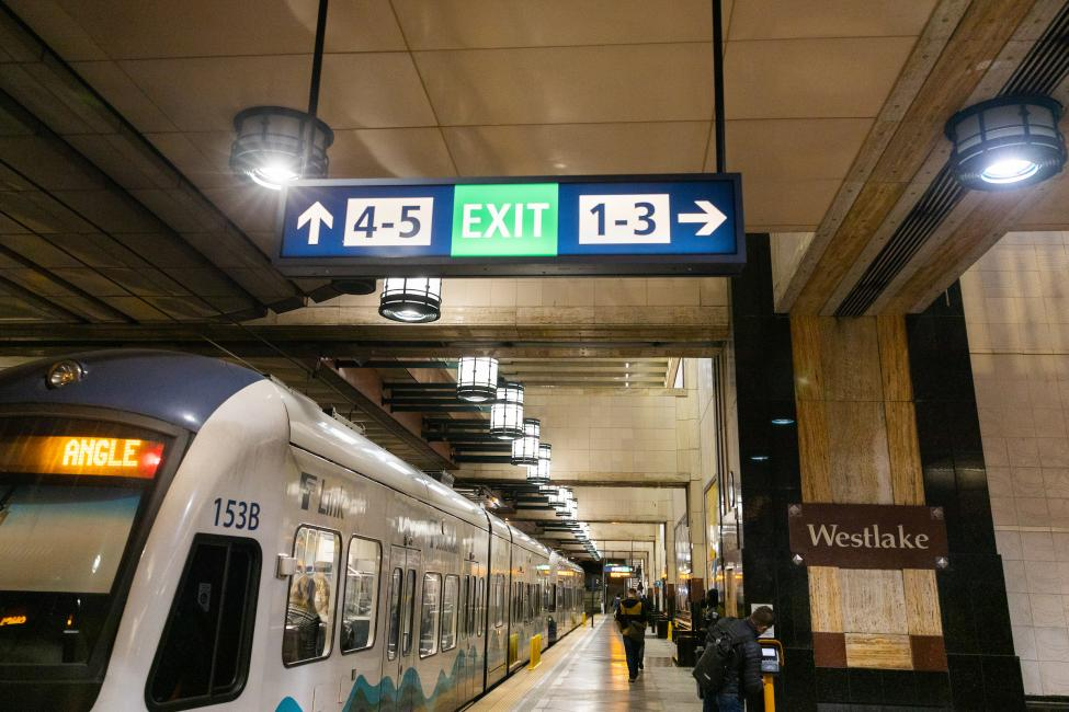 New overhead signage in Westlake Station displays a large green 'exit' icon and points riders to numbered exits (1 through 5).