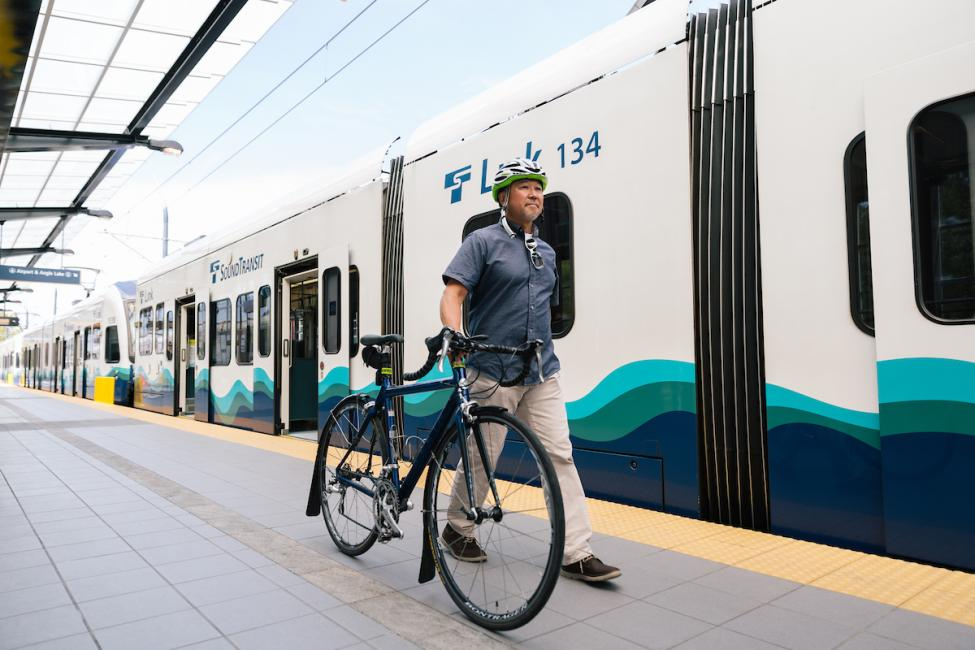 A rider approaching Link train at Angle Lake Station with his bike.