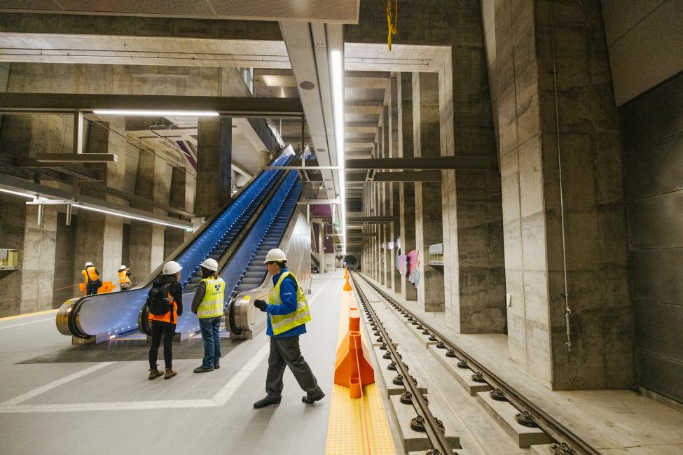 People in hard hats stand on the platform of Roosevelt Station at the base of newly installed escalators.