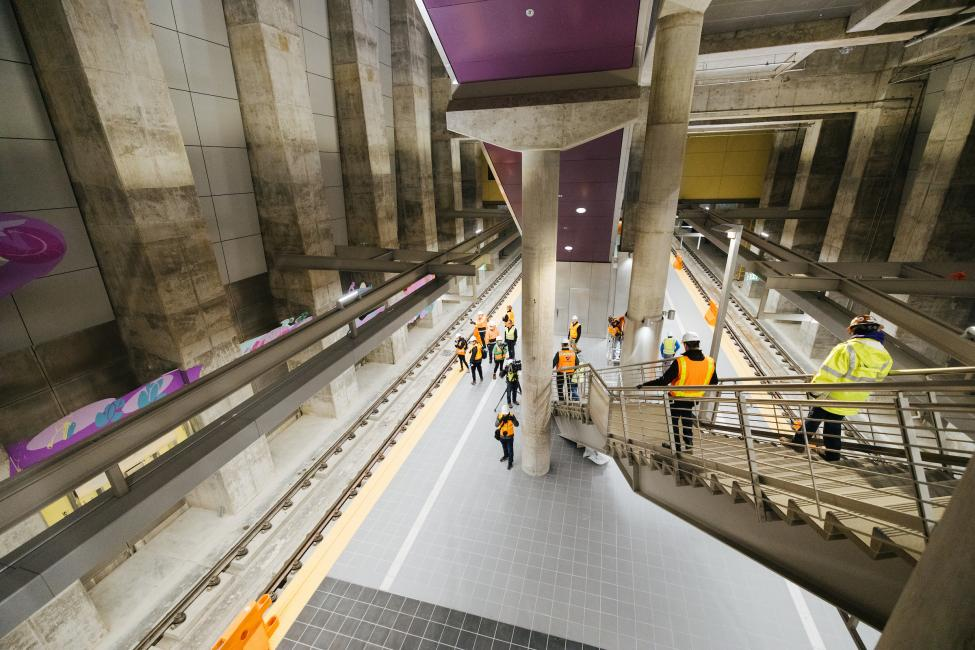 Looking down at the platform of the nearly complete Roosevelt Station, as media members descend the stairs.