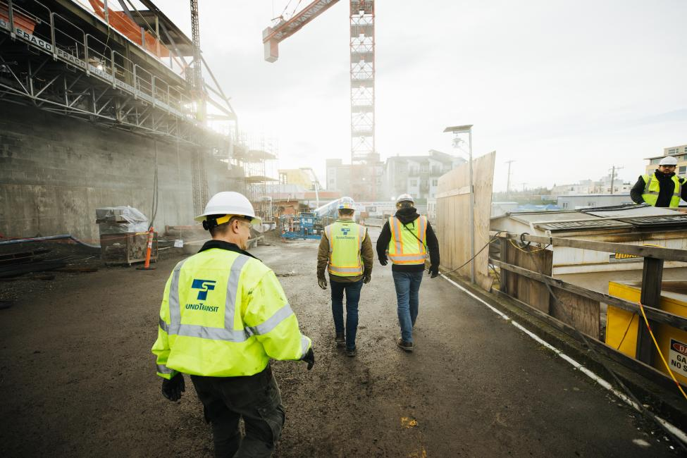 Three men in yellow vests walk toward the construction site at Roosevelt Station.