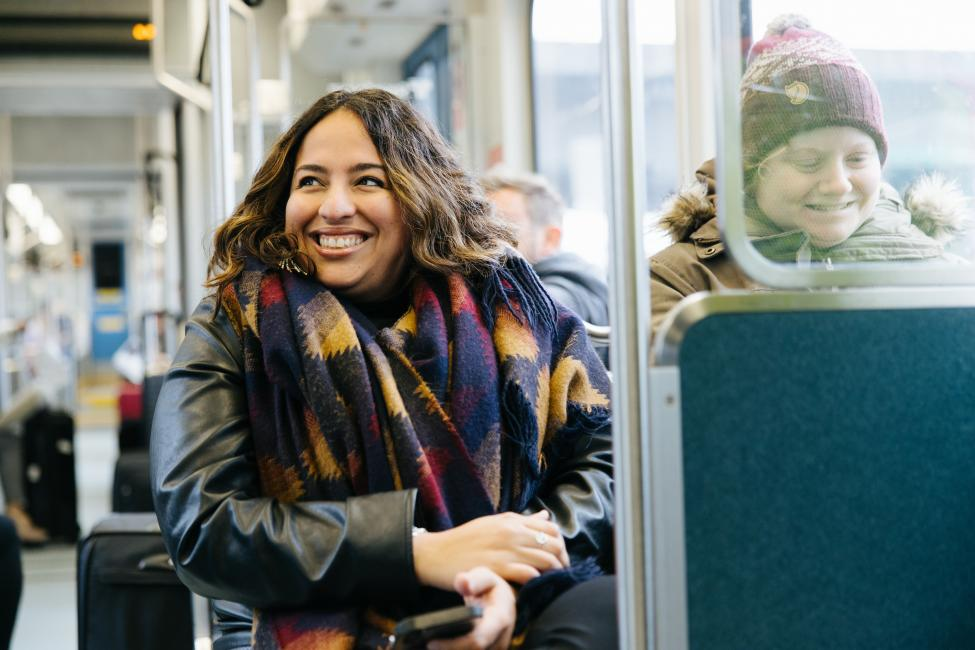 Two riders smile onboard Link light rail.