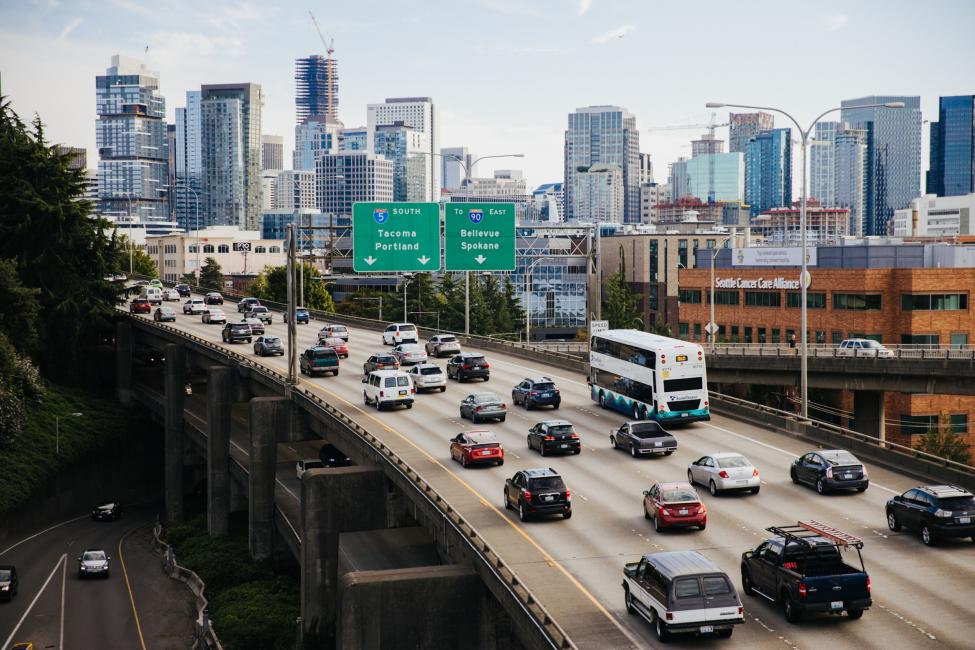 Cars and an ST Express Bus drive on I-5 South, with part of the Seattle skyline in the background.