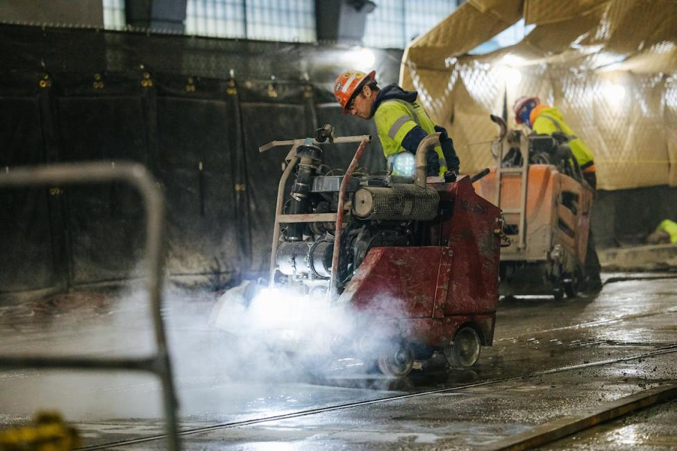 Workers in the construction area south of International District/Chinatown Station using machinery to remove concrete for new rails.