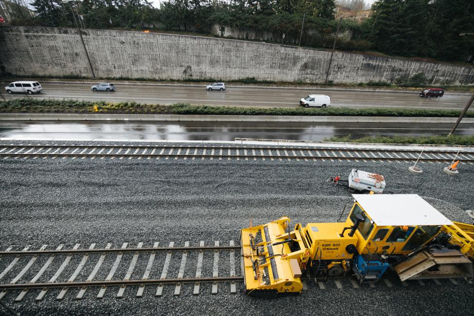A large piece of construction equipment is pictured on the rails next to I-90 in Mercer Island.