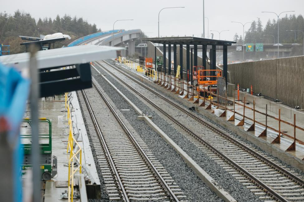 The platform and rail at Overlake Village Station, with SR-520 in the background.