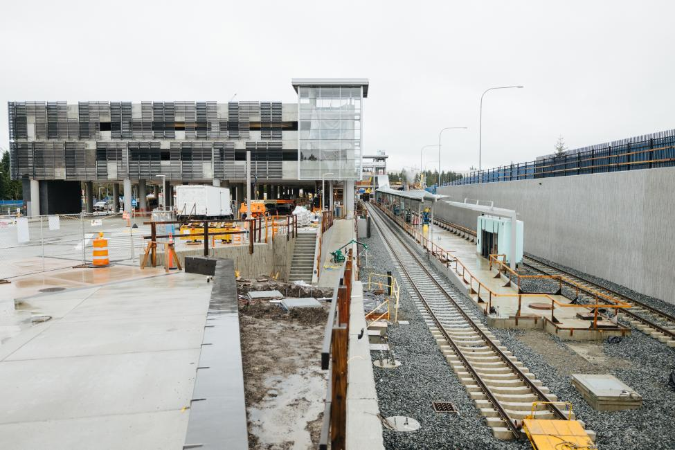 Construction fencing surrounds a new parking garage and future light rail station at Redmond Technology Center.