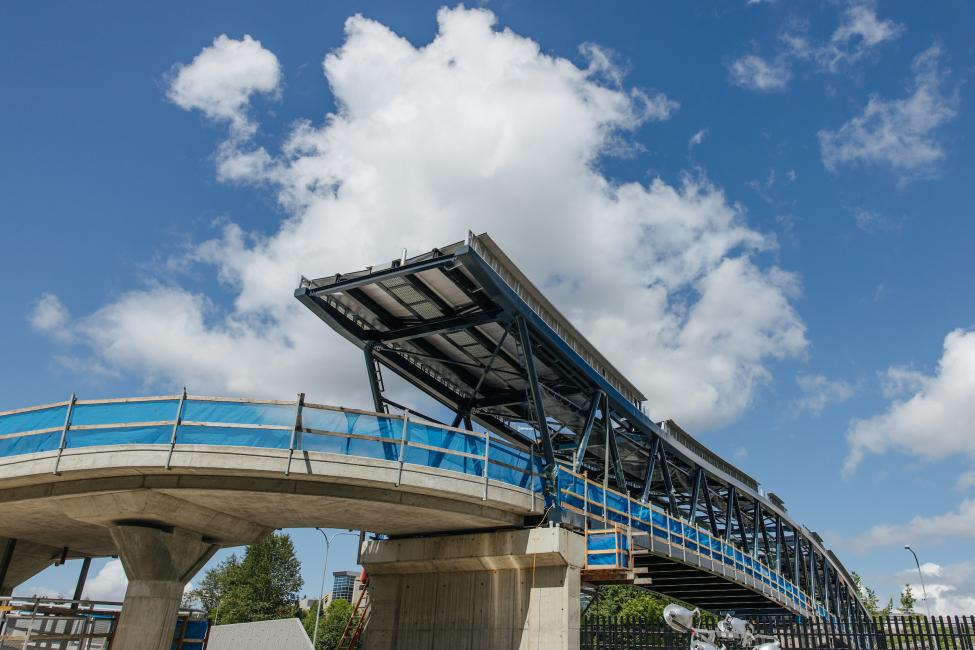Blue skies and white clouds can be seen in the background of this photo of the entrance to the new pedestrian bridge at Overlake Village Station.