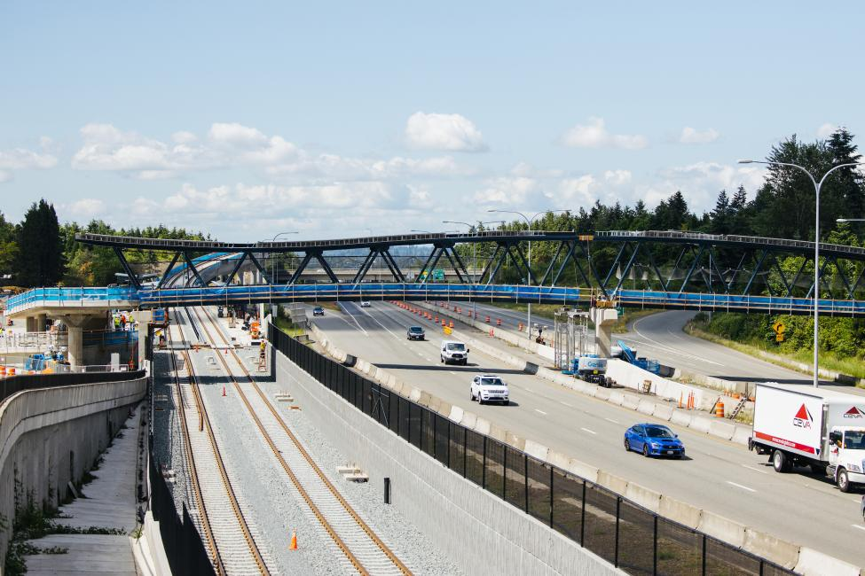 A large bridge crosses over highway SR 520 in Redmond. Several cars are driving on the road. New tracks for light rail can also be seen on the south side of the freeway.
