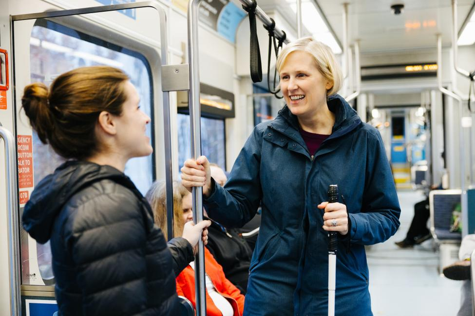 Jodi Mitchell holds a white cane and chats with a fellow passenger while standing on a Link train.